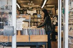 De vrouw doorbladert vinylverslagen bij een opslag in Notting-Heuvel, Londen royalty-vrije stock afbeelding