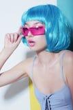 De vrouw draagt Blauwe Glanzende Pruik en Roze Glazen Stock Afbeeldingen