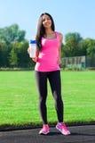 De vrouw drinkt de sport van de waterfles op stadion Stock Fotografie