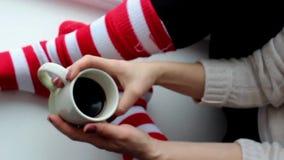 De vrouw drinkt heldere sokken van de koffie de houten lijst stock videobeelden