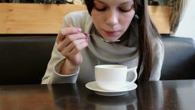De vrouw drinkt hete thee van kop met een lepel Sluit omhoog handen en gezicht stock footage