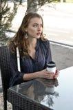 De vrouw drinkt koffie in een openluchtkoffie stock foto's