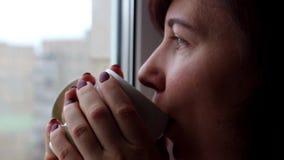 De vrouw drinkt koffie houten lijst stock footage