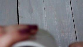 De vrouw drinkt koffie houten lijst stock video