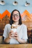 De vrouw drinkt milkshake die prachtig met room en koekjes wordt verfraaid royalty-vrije stock afbeeldingen