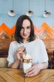De vrouw drinkt milkshake die prachtig met room en koekjes wordt verfraaid stock foto's