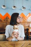 De vrouw drinkt milkshake die prachtig met room en koekjes wordt verfraaid royalty-vrije stock foto's