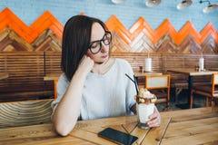De vrouw drinkt milkshake die prachtig met room en koekjes wordt verfraaid royalty-vrije stock fotografie