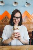 De vrouw drinkt milkshake die prachtig met room en koekjes wordt verfraaid stock fotografie