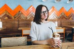 De vrouw drinkt milkshake die prachtig met room en koekjes wordt verfraaid stock afbeelding