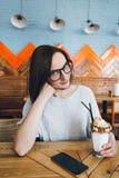 De vrouw drinkt milkshake die prachtig met room en koekjes wordt verfraaid stock afbeeldingen