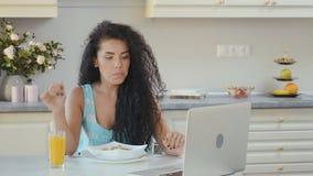 De vrouw drinkt sap tijdens ontbijt en let op de film op laptop stock footage