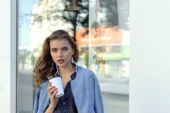 De vrouw drinkt sap van een document kop stock foto