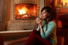 De vrouw drinkt thee en verwarmt zich door de open haard Het jonge Kaukasische wijfje houdt kop thuis van koffie warm Royalty-vrije Stock Fotografie