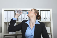 De vrouw drinkt water in het bureau Stock Fotografie