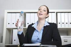 De vrouw drinkt water in het bureau Stock Afbeeldingen