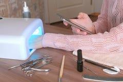 De vrouw droogt haar spijkers met schellak in UVlamp en doorbladerend Internet in mobiele telefoon close-uphand stock afbeelding