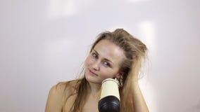 De vrouw droogt nat haar met een droogkap stock video