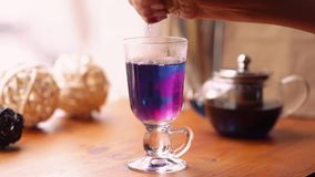 De vrouw drukt een citroen in a van blauwe Thaise thee Blauwe theereactie op citroensap De blauwe thee draait purper Langzame Mot stock videobeelden