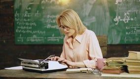 De vrouw drukt tekst op een schrijfmachine bij de lijst met een bos van boeken op de achtergrond van een schoolraad Schrijfmachin stock video