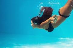 De vrouw duikt in pool royalty-vrije stock fotografie