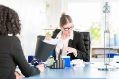 De vrouw in een bureau zoekt een verloren nota in de document bak stock fotografie