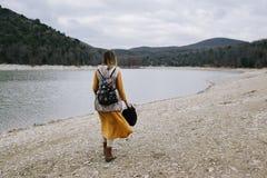 De vrouw in een gele kleding en met bloemenrugzak loopt langs de meerkust royalty-vrije stock afbeeldingen