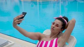 De vrouw in een gestreept zwempak ligt door de pool in een gestreept zwempak stock video