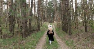 De vrouw in een hoed gaat in het hout stock videobeelden