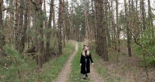 De vrouw in een hoed gaat in het hout