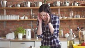De vrouw in een overhemd met een slechte hoofdpijn in de keuken snijdt groenten stock footage