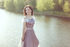 De vrouw in een purpere kleding glimlacht royalty-vrije stock fotografie