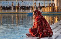 De vrouw in een rode saree zit en bidt in Gouden Tempel in de vroege ochtend amritsar India Stock Foto
