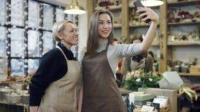 De vrouw in een schort en het meisje in een schort maken samen selfie, zij embrance stock video