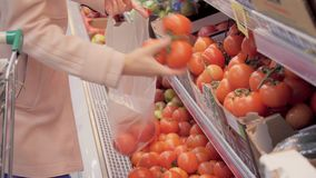 De vrouw in een supermarkt selecteert de tomaten stock footage