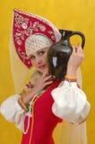De vrouw in een volks Russische kleding houdt een kruik Stock Foto's