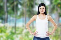 De vrouw is in een wit mouwloos onderhemd en jeans De bomen en het overzees zijn op de achtergrond in onduidelijk beeld Stock Foto's