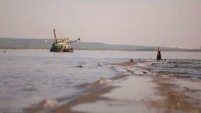 De vrouw in een zwarte kleding gaat langs de kustlijn op de achtergrond van water, de stad en het industriële schip stock video