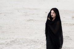 De vrouw in een zwarte kleedt zich in een woestijn royalty-vrije stock foto