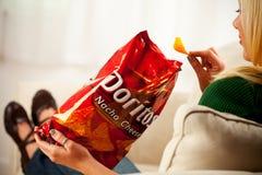 De vrouw eet Chip From Bag Of Doritos, Geproduceerd door Frito leg C Royalty-vrije Stock Foto's