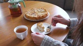 De vrouw eet eigengemaakte appeltaart en drinkt een thee Het proces van spijkers stock videobeelden