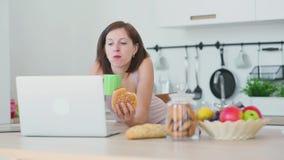 De vrouw eet hamburger en werkt met laptop stock videobeelden