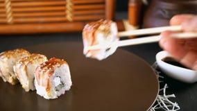 De vrouw eet Japans voedsel De smakelijke broodjes worden genomen met houten stokken en in sojasaus ondergedompeld stock video