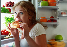 De vrouw eet nacht stal de ijskast Royalty-vrije Stock Foto