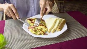 De vrouw eet omelet met ham en toostclose-up van het eatting van ontbijt stock footage