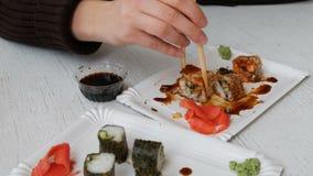 De vrouw eet Sushibroodjes met Eetstokjes in een Japans Restaurant stock footage