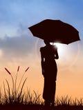 De vrouw en de zonsondergang van de paraplu Royalty-vrije Stock Afbeelding