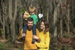 De vrouw en de echtgenoot met weinig babyzoon genieten van zonnige dag in park, genetische verhouding Familieverhouding Uit voor  royalty-vrije stock fotografie