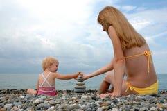 De vrouw en het kind bouwen piramide Royalty-vrije Stock Afbeelding