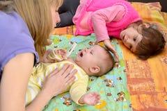 De vrouw en het meisje kalmeren de zieke schreeuwende baby royalty-vrije stock foto's